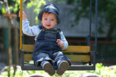 Cute little boy playing on the swings — Stock Photo
