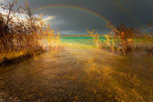 Rainbow and dark clouds over large lake — Stock Photo