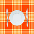 Stock Photo: Dinner plate, knife and fork over orange tablecloth