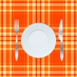 Dinner plate, knife and fork over orange tablecloth - Stock Photo