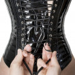 Stock Photo: Male hands tightening up corset