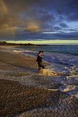 Kvinnan promenader på stranden ensam — Stockfoto