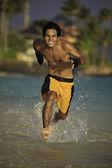 Asian man running on a hawaii beach — Stock Photo