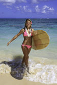 Teenager walking her surfboard from the ocean — Stockfoto