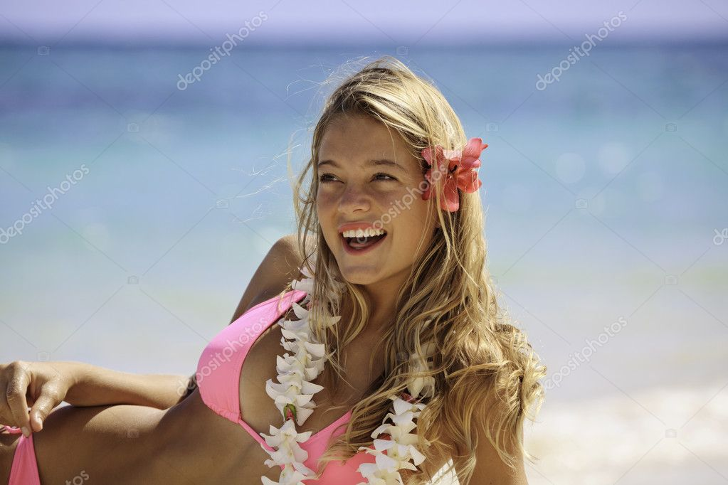Teenage girl in pink bikini and flower lei at the beach in hawaii