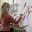 Artist in her fifties painting on canvas — Foto Stock