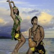 Couple dancing hula by the ocean - Stock Photo