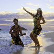 Stock Photo: Couple dancing hula by the ocean
