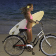Girl in pink bikini riding her bike on the beach - 图库照片