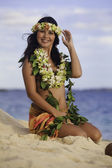 Hula dancer sitting on the beach — Stock Photo