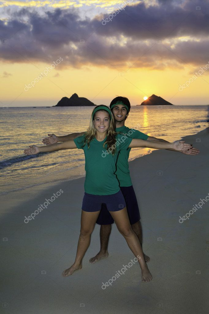 Young couple doing yoga, stretches, and meditation on the beach at sunrise — Stock Photo #4906379