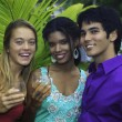 Three friends at a barbecue party in hawaii — Stock Photo