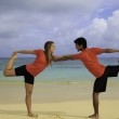 Couple on the beach exercising at sunrise — Stock Photo #5061264