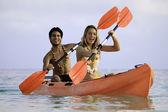 Couple paddling their kayak — Stock Photo