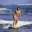 Girl in pink bikini surfing - Stock Photo