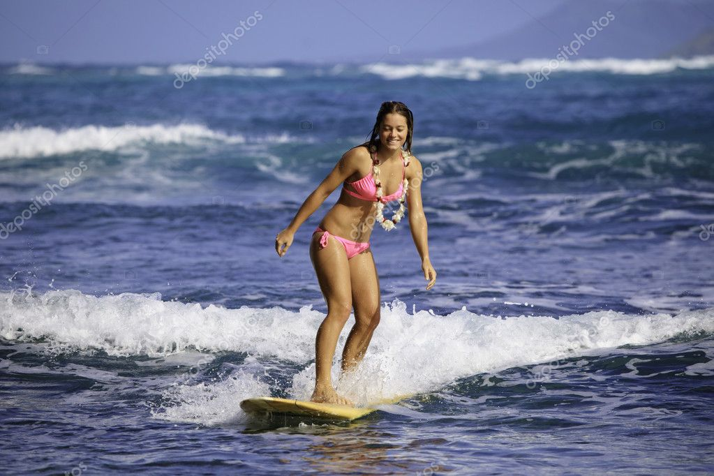 Teenage girl in pink bikini and flower lei surfing in hawaii — Stock Photo #5235763
