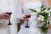 The groom and the bride with red wine glasses — Stock Photo