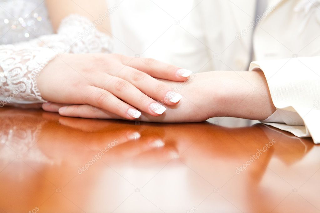 Hands of the groom and the bride lying on a table with colors  Stock Photo #4373109