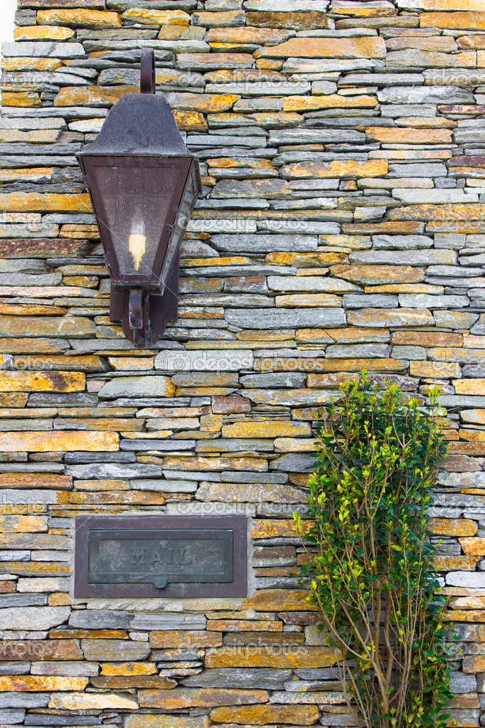 Porch light and mail slot are the details on a stone house — Stock Photo #5244131