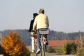 An old married couple ride with bicycle — Stock Photo
