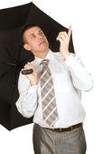 The businessman under an umbrella — Stock Photo