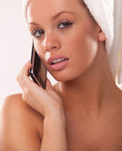 Woman after bath using her mobile phone — Stock Photo