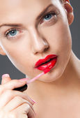 Applying lip gloss — Stock Photo