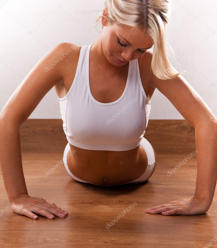 Photo of young girl doing difficult exercise for arm biceps on the floor — Stock Photo #4510431