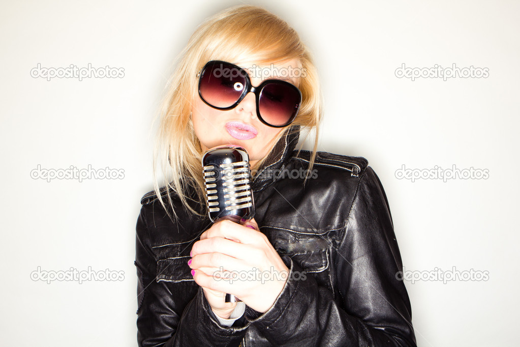 Blonde pop star on pink background singing , holding retro mic  — Stock Photo #5001822