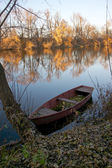 Autumn landscape of the river with an old boat — Stock Photo