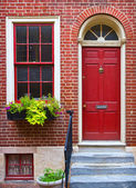 Three windows and a door in brick wall — Stock Photo