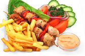 Shashlik with french fries — Stock Photo