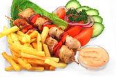 Shashlik with french fries — Stock Photo
