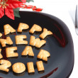 Royalty-Free Stock Photo: Black plate with cookies, fork and new year decoration