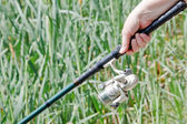 Fisherwoman hand holding a fishing rod — Stock Photo