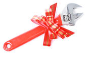 Wrench with red plastic handle and red bow as a gift for handyman — Stock Photo