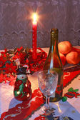 New Year's setting with wine, glass, tangerines, christmas decor — Stock Photo