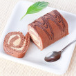 Royalty-Free Stock Photo: Swiss roll with condensed milk cream and a green leaf