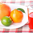 Tangerine, grapefruit and lime on white plate with glass of red orange juic — Stock Photo
