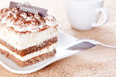 Portion of tiramisu dessert and a cup of coffee — Stock Photo