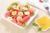 Fresh fruits salad on white plate with honey — Stock Photo