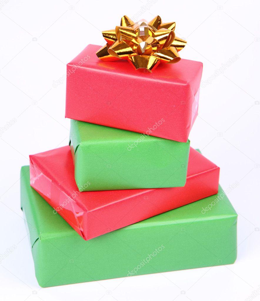 在带有金色蝴蝶结白底绿色和红色包装的礼品– 图库图片
