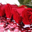 Red roses and confetti - Stock Photo