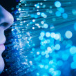 Young woman`s face and blue fiber optics — Stock Photo