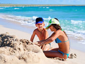 Two kids playing in sand at the beach — Stock Photo