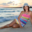 Woman in a colorful dress and hat on the beach — Stock Photo