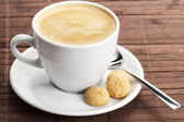 Coffee in a white cup with amarettini and spoon — Stock Photo