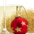 Stock Photo: Red christmas ball near glass with champagne, angels hair in front of a cha
