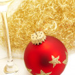 Red christmas ball from top with angels hair and a champagne glass — Stok fotoğraf