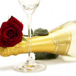 Wet red rose on a champagne bottle behind a champagne glass — Stock Photo